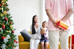 Familj som dekorerar en julgran och en fader som ger julG arkivbilder