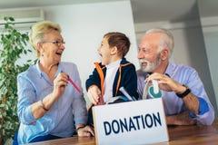 Familj som donerar oönskade objekt arkivbild