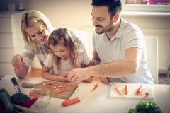 Familj som förbereder sallad arkivfoton