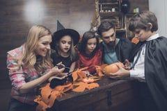 Familj som förbereder sig för allhelgonaaftonpartiet Barn och deras föräldrar klippta ut slagträn från papper royaltyfria bilder