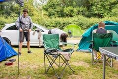 Familj som förbereder tältet arkivfoto