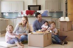 Familj som firar att flytta sig in i nytt hem med pizza arkivbild