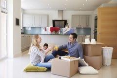 Familj som firar att flytta sig in i nytt hem med pizza royaltyfria bilder