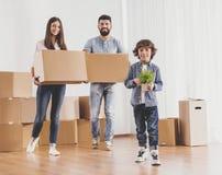 Familj som flyttar sig till det nya stället och ställningar med askar Royaltyfria Bilder
