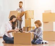 Familj som flyttar sig till nya ställe- och emballageaskar Royaltyfri Fotografi