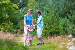 Familj som fotvandrar i ett sörjaträ Fotografering för Bildbyråer