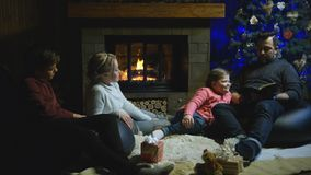 Familj som framme kopplar av av julgranen Arkivbilder