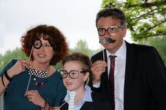 Familj som framme poserar av ett fotobås Arkivbild