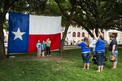 Familj som framme tar ett foto av Texas Flag i de Fort Worth kreatursinhägnaderna, Forth Worth, Texas Royaltyfri Fotografi