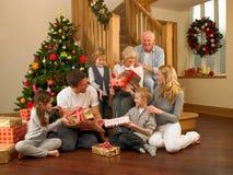 Familj som framme utbyter gåvor av julgranen Royaltyfri Fotografi