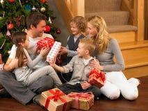 Familj som framme utbyter gåvor av julgranen Royaltyfria Foton