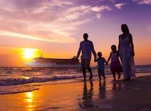Familj som går begrepp för ferie för strandsolnedgånglopp royaltyfri fotografi