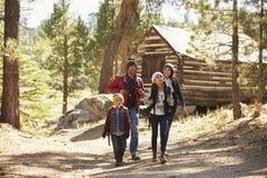 Familj som går i väg från en journalkabin i en skog Fotografering för Bildbyråer
