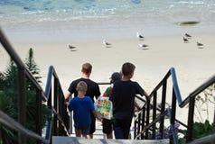 Familj som går ner trappa till stranden i Laguna Beach, Kalifornien Fotografering för Bildbyråer