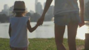 Familj som går på parkera med sjön och skyskrapor på bakgrunden stock video