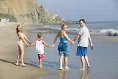 Familj som går på stranden royaltyfri fotografi