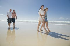 Familj som går på strandholdinghänder Arkivbild