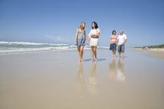 Familj som går på strandholdinghänder Royaltyfria Bilder
