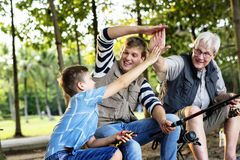 Familj som gör höga fem, medan fiska Royaltyfria Bilder