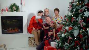 Familj som gör Selfie nära julgranen lager videofilmer