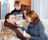 Familj som ger preventivpillerar till den sjuka mannen Royaltyfri Foto