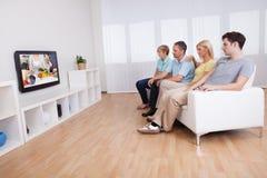Familj som håller ögonen på den widescreen televisionen Arkivbild