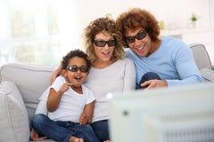 Familj som håller ögonen på filmen 3D Arkivbilder