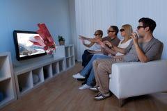 Familj som håller ögonen på televisionen 3D Arkivfoton
