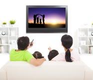 Familj som håller ögonen på tv:n Arkivfoton