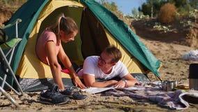 Familj som har bygdpicknicken med tältet stock video