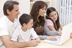Familj som har den roliga användande bärbar datordatoren hemma Arkivfoton