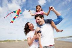 Familj som har den roliga flygdraken på strandferie Royaltyfria Bilder