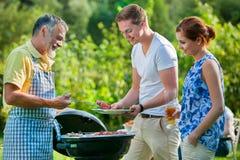 Familj som har en grillfestdeltagare Arkivbilder