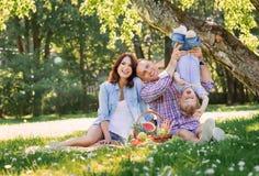 Familj som har en picknick i parkera Royaltyfri Fotografi