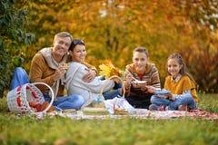 Familj som har en picknick i parkera Fotografering för Bildbyråer