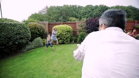Familj som har en vattenkamp i trädgården arkivfilmer