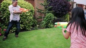 Familj som har en vattenkamp i trädgården stock video