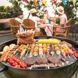 Familj som har ett grillfestparti i deras trädgård arkivfoto
