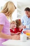 Familj som har frukosten i kök för skola arkivbilder