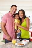 Familj som har frukosten i kök tillsammans Arkivfoto