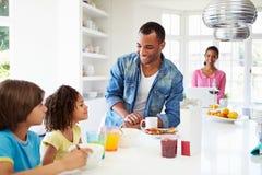 Familj som har frukosten i kök tillsammans Arkivfoton
