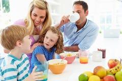 Familj som har frukosten i kök tillsammans