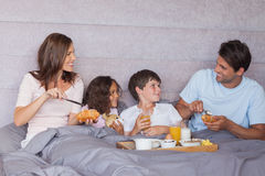 Familj som har frukosten i säng Arkivbilder