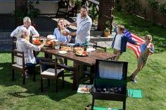 Familj som har grillfesten, medan fira 4th juli tillsammans Arkivbild