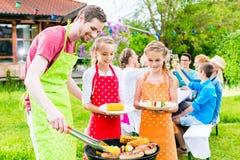 Familj som har grillfesten på det trädgårds- partiet Royaltyfri Foto