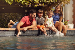 Familj som har gyckel av deras simbassäng Arkivfoton