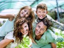 Familj som har gyckel i ett växthus Arkivbilder