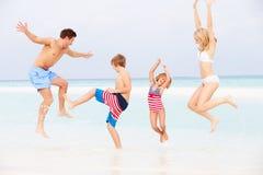 Familj som har gyckel i havet på strandferie Arkivbilder