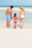 Familj som har gyckel i havet på strandferie Arkivfoto