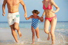 Familj som har gyckel i havet på strandferie Royaltyfri Fotografi